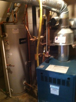 An indirect water heater: the blue boiler heats water in a pipe that runs in a coil through the storage tank for both space and domestic hot water heating.