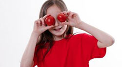 girl with tomatoes in front of eyes